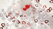 Stock Video Footage of small red hearts fall on a two wineglass.Valentines day theme.  HD
