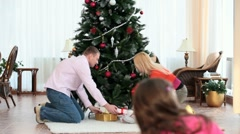 Putting gifts under fir-tree Stock Footage