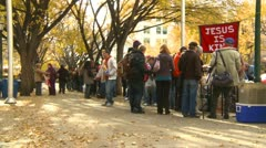 People lined up for street church meal Stock Footage