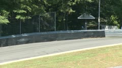 Race cars going by guard rail Stock Footage