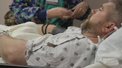 Nurse checks patients blood pressure after surgery Stock Footage