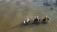 Kids in baskets with snakes on Tonle Sap Lake, Cambodia Stock Footage