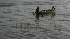 Women rowing in boat with fruits on Tonle Sap Lake, Cambodia. - stock footage