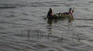 Stock Video Footage of Women rowing in boat with fruits on Tonle Sap Lake, Cambodia.