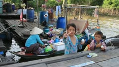 Kids eating eggs around floating village on Tonle Sap Lake, Cambodia Stock Footage