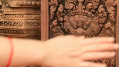 Woman's hand touching carving of Angkor Temple, Banteay Srey - stock footage