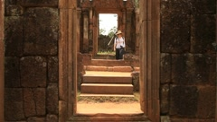 Woman walking and sitting on stone in Angkor Temple, Banteay Srey Stock Footage