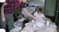 Stock Video Footage of Father Lights Birthday Cake Candles Circa 1960 (Vintage Film Home Movie) 2000