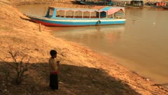 Boy in shade around floating village on Tonle Sap Lake, Cambodia Stock Footage