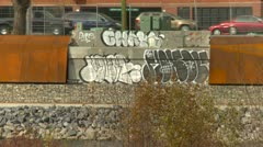 Graffiti on wall with traffic in bg Stock Footage
