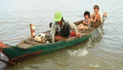 Men bailing water out of boat on Tonle Sap Lake, Cambodia Stock Footage