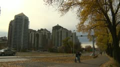 People bicycling and walking on path late fall Condos, downtown Calgary Stock Footage