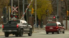 Downtown traffic and LRT Siemans SD60 train at level crossing, Calgary, Alberta Stock Footage