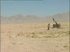 Stock Video Footage of Taliban artillerymen firing Howitzer in Afghanistan desert.