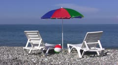 Chaise lounges and umbrella on a beach Stock Footage