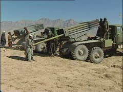 Taliban artillerymen load rockets into launchers in Afghanistan desert. - stock footage