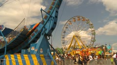 Midway rides at fairgrounds - Turbo Loop and Ferris Wheel Stock Footage