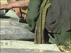 Taliban arm rockets by screwing on the detonators. Stock Footage