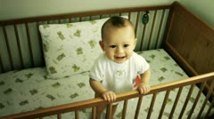 Cute baby standing in cot smiling - stock footage