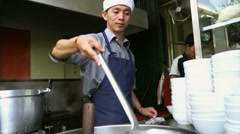 Man working as cook in Asian restaurant kitchen Stock Footage