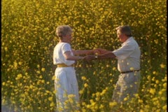 A mature couple spin while holding hands in a field of yellow wildflowers. Stock Footage