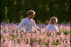 A young couple walks in a field of purple wildflowers - stock footage