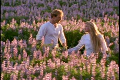 A young couple walks in a field of purple wildflowers Stock Footage