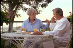 A senior couple have breakfast in an outdoor setting - stock footage