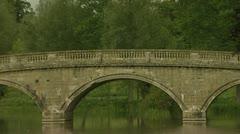 Caravan crossing old stone bridge spanning still river on gloomy day. Stock Footage