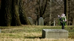 Grave with flowers and American flag pan shot Stock Footage