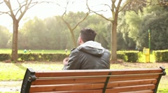 Guy at park with mp3 player - stock footage