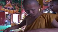 Stock Video Footage of Young Thai Buddhist monks dressing in saffron robes for the first time.