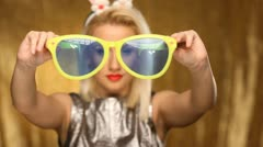 Beautiful blond party girl dancing with giant sunglasses and bunny ears Stock Footage