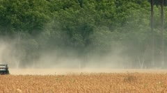 Combine harvesting soybeans in agricultural field - stock footage