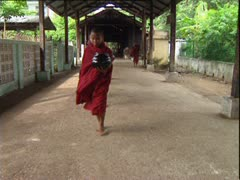Barefoot, robed young boy monks filing out of Burmese temple to collect alms. Stock Footage