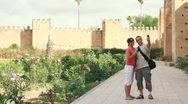 Happy tourist couple taking photo with cellphone near ancient walls HD Stock Footage