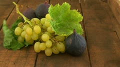 Green grapes and figs on wooden table - stock footage