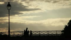 People silhouetted on a bridge in Paris Stock Footage