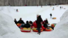 People going down a hill on a sled (focus on foreground) - stock footage