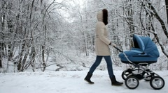 Young mother with baby carriage walking in the winter park - stock footage
