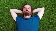 Young guy sleeps on grass Stock Footage