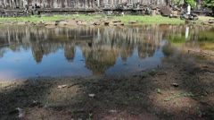 Ancient Temple (Angkor) - WS tilt up to Bayon from pool II Stock Footage