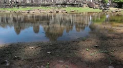 Ancient Temple (Angkor) - WS tilt up to Bayon from pool Stock Footage
