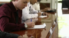 Young white collar worker taking notes in meeting room during conference - stock footage