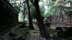Ancient Temple (Angkor) - Pan from trees to broken yard Stock Footage
