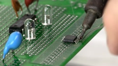 Soldering surface mount IC to circuit by hand - stock footage