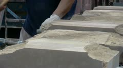 Craftsman shaping stone with chisel on an assembly conveyor line Stock Footage