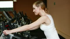 Happy woman using hometrainer in gym Stock Footage