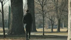 Guy all alone walking in the park - stock footage