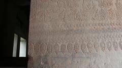 Ancient Temple (Angkor) - tilt up to detailed wall carving at Angkor Stock Footage